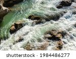 Close-up abstract texture above view of river torrent and clear fresh cold water flowing through mountain rocks in valley with foam and bubbles on sunny day. Nature force and power background