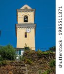 Old tower church with clock and bell in Cinque Terre National Park in Italy on city hill. Sunny landscape during the holidays. July 3, 2018 Cinque Terre National Park, Italy