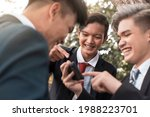 Small photo of Three friends chuckle over a funny viral video on social media playing on a cellphone. Bonding among young asian men outdoors.