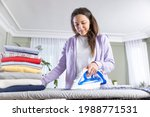 Young Woman Ironing The Clothes ...