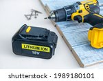 Small photo of Close up 18 volt recharge Li-ion battery for electric cordless tool,saw,rotary hammer,drill,jigsaw,wrench on white.Blurred screwdriver,screws on gray-painted boards behind.Selective focus, copy space
