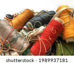 Piles of colorful threads mixed with sewing equipment, looks messy