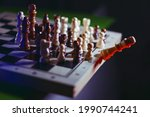 Small photo of The overthrow of the king. Revolt and unification of whites and blacks against the king. Allegory in chess.