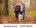 Stock photo couple walking dog through winter woodland 199078004