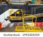 Small photo of There are gangway of ship with net and yellow portable ladder on container terminal. The yellow portable ladder is connected with gangway of ship due to long distance between ship and terminal.