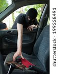 A thief steals someone's phone from the car - stock photo