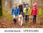 Stock photo family walking dog through winter woodland 199351385