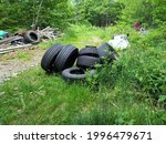 An abandoned lot of land in rural Nova Scotia where garbage is disposed of illegally. The trash includes tires, old cars, planks of wood, and other unusable items related to transportation.