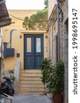 Destination Syros island, Cyclades, Greece. Stone stairs drives to half opened house entrance at capital of Siros Hermoupolis background. Empty cobblestone narrow yard staircase summer day. Vertical.