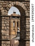 Bell tower and stork nests of the church Santos Justo y Pastor, through an arch of the Aqueduct of Segovia