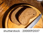 Still life - yeast-free buckwheat bread, various types of black bread, a knife, and a linen napkin on a wooden board, a wooden background, hard light, a photo in a low key