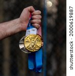 Small photo of April 17, 2021 Tokyo, Japan. Gold, silver and bronze medals of the XXXII Summer Olympic Games in Tokyo in the hand of an athlete.