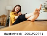 Small photo of Cute sincere young woman looking at camera with an impish grin and laughing eyes as she relaxes with her bare feet up on the table at home