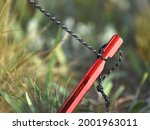 Small photo of Tent peg or anchor closeup. A method of attaching a sling when setting up a tent. Red peg anchor in the ground with strong fastening tent. Protecting tent roofs from wind and rain.