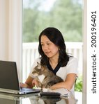 Stock photo vertical image of mature woman and her cat both looking at laptop screen while working from home 200196401