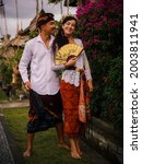 Small photo of Balinese culture. Multicultural couple wearing traditional Balinese clothing. Charming woman holding beautiful fan. Caucasian wife and Balinese husband. Romantic relationship. Penglipuran, Bali