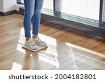 Small photo of Weight loss. Cropped slim lady standing on weighing scale, checking weigh at home, smart weigh scales help woman to keep fit, to monitor weight