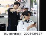 asian hairdresser cutting... | Shutterstock . vector #2005439837
