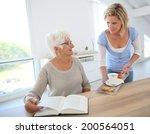 home helper giving tea to... | Shutterstock . vector #200564051