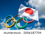 Small photo of RIO DE JANEIRO - MARCH, 2016: A Japanese flag flutters in the wind in front of Olympic Rings standing under bright blue sky with puffy white clouds