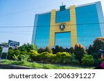 Small photo of Yogyakarta, Indonesia - June 2021: RS Hermina Yogyakarta or Hermina Hospital building. Front view facade with beautiful shrubs