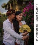 Small photo of Balinese culture. Portrait of multicultural couple wearing Balinese clothing. Charming woman holding beautiful fan. Balinese husband hugging Caucasian wife. Romantic relationship. Penglipuran, Bali
