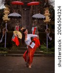 Small photo of Beautiful woman dancing traditional Balinese dance in front of the temple gate. Caucasian woman wearing Balinese clothes. Culture and religion. Penjor bamboo and umbrella decoration. Penglipuran, Bali