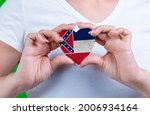 Woman in white t-shirt holds a heart in the form flag Mississippi on her chest. Photo for a postcard on Flag Day, Independence Day, travel, patriotism, other holiday