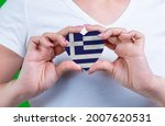 Woman in white t-shirt holds a heart in the form flag Greece on her chest. Photo for a postcard on Flag Day, Independence Day, travel, patriotism, other holiday