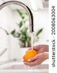 Female Washing Fresh Orange In...
