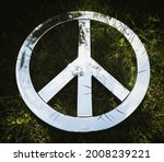 Wide close up of a Highly Chrome colored Anti War, Anti Nuclear Peace Sign set against a Dark green background with sky and grass reflections and shadows.