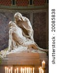 Small photo of Statue Pieta in chapel of romanesque St. Gereon church in Cologne with candles and candlelight.