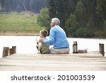 senior man fishing with grandson | Shutterstock . vector #201003539