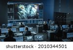 Small photo of Group of People in Mission Control Center Establish Successful Video Connection on a Big Screen with an Astronaut on Board of a Space Station. Flight Control Scientists Sit in Front of Computers.