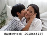 Son Kissing Mom On White Bed In ...