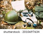 Russian Soviet Portable Radio Transceiver Used By USSR Red Army Signal Corps In World War Ii. Headphones, Telegraph Key And Helmet Are On A Forest Stump.
