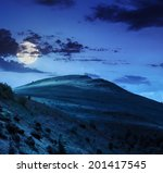 slope of mountain range with coniferous forest and village at night in moon light - stock photo