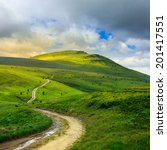 summer landscape. mountain path through the field turns uphill to the sky - stock photo