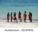 Diani Resort (30 km south of Mombasa), Kenya, Africa 02 May 2007 : Group of male Masai on a beautiful kenyan beach in traditional clothes. Amaizing colors - light sand blue sky and turquoise ocean. - stock photo