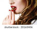 Sexy girl eating chocolate woman holding chocolate in her mouth red lipstick lipgloss makeup - stock photo