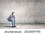 young woman sitting on chair in ... | Shutterstock . vector #202009795