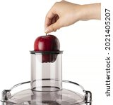 Small photo of Woman's hand putting an apple in a juicer on a white background