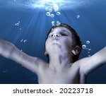An underwater scene with sun rays shining on a boy trying to reach the surface - stock photo