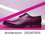 Brown leather men's shoes with violet neon light lamp over lavender and violet background. Vogue style. Art fashion studio shot - stock photo