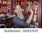 beautiful girl bartender at the ... | Shutterstock . vector #202317475