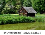A close up on a wooden shack, hut, or house standing next to a small pond, lake, or swamp covered with shrubs, reeds and other flora seen on a sunny summer day near a dense forest or moor in Poland