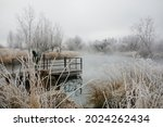A Fisherman On A Dock On A Cold ...