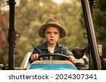 A Young Boy In A Hat Driving A...