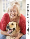 Stock photo senior woman at home with dog 202530901