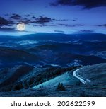 mountain range summer landscape. valley with stones and road on the hillside. forest on the mountain under the beam of light falls on a clearing at the top of the hill at night in moon light - stock photo